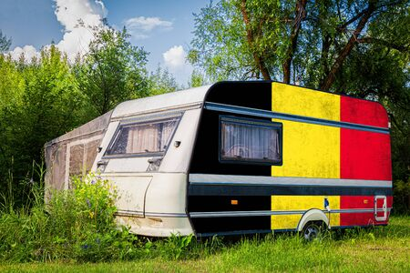 A car trailer, a motor home, painted in the national flag of  Belgium stands parked in a mountainous. The concept of road transport, trade, export and import between countries. Standard-Bild - 129846765
