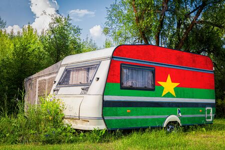 A car trailer, a motor home, painted in the national flag of  Burkino faso stands parked in a mountainous. The concept of road transport, trade, export and import between countries. Standard-Bild - 129846773