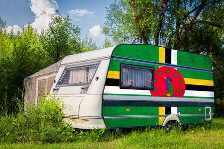 A car trailer, a motor home, painted in the national flag of  Dominica stands parked in a mountainous. The concept of road transport, trade, export and import between countries. Standard-Bild - 129846778