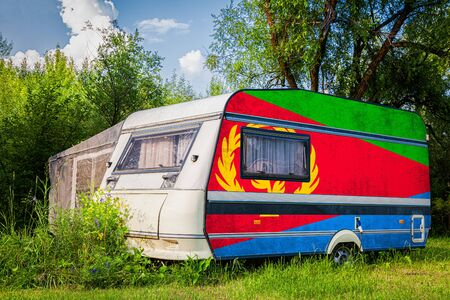 A car trailer, a motor home, painted in the national flag of  Eritrea stands parked in a mountainous. The concept of road transport, trade, export and import between countries. Standard-Bild - 129846779