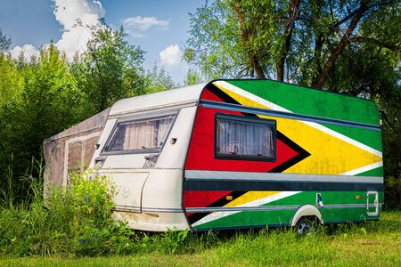 A car trailer, a motor home, painted in the national flag of Guyana stands parked in a mountainous. The concept of road transport, trade, export and import between countries. Standard-Bild - 129846875