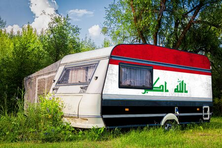 A car trailer, a motor home, painted in the national flag of  Irak stands parked in a mountainous. The concept of road transport, trade, export and import between countries. Standard-Bild - 129844608