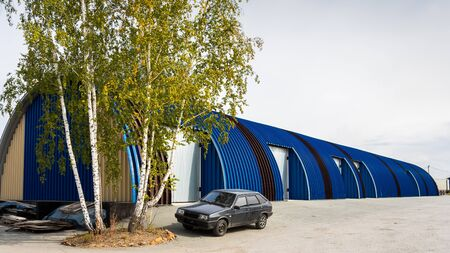 Facade on large industrial building made of metal white and blue panels. Industrial concept of transportation, loading and storage of goods. The car is in the loading area