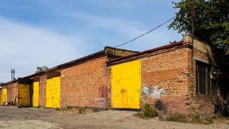 Facade of a yellow metal warehouse, a commercial building with entrances for cars for storing goods. The concept of storage of goods by importers, exporters, wholesalers, transport enterprises, custom 스톡 콘텐츠
