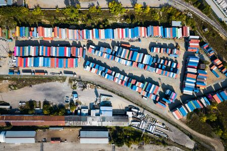 Top view of logistics center, a large number of containers of different colors for storing goods. The concept of storage of goods by importers, exporters, wholesalers, transport enterprises, customs