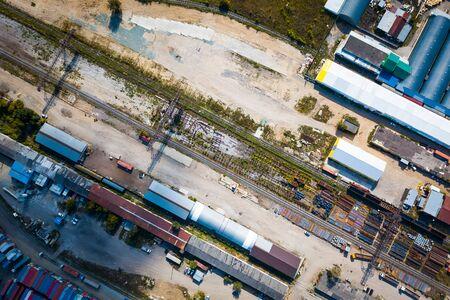 Draufsicht auf das Industriegebiet: Eisenbahnschienen, Garagen, Lagerhallen, Container zur Lagerung von Waren. Das Konzept der Warenlagerung durch Importeure, Exporteure, Großhändler, Transportunternehmen, Zoll