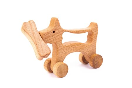 Photo of a wooden dog with bone on wheels  of beech. Toy made of wood  on a white isolated background.A toy for entertaining children and resting parents 写真素材