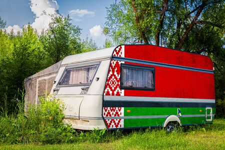 A car trailer, a motor home, painted in the national flag of  Belarus stands parked in a mountainous. The concept of road transport, trade, export and import between countries. Stock Photo
