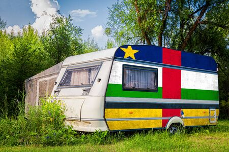 A car trailer, a motor home, painted in the national flag of  Central African Republic stands parked in a mountainous. The concept of road transport, trade, export and import between countries.