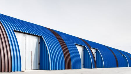 Facade on large industrial building made of metal blue panels. Industrial concept of transportation, loading and storage of goods