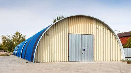 Facade of a blue metal warehouse, commercial building for storage of goods. The concept of storage of goods by importers, exporters, wholesalers, transport enterprises, customs