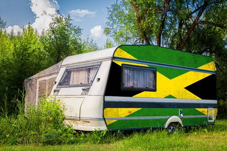 A car trailer, a motor home, painted in the national flag of Jamaica stands parked in a mountainous. The concept of road transport, trade, export and import between countries.