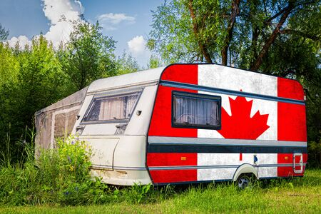A car trailer, a motor home, painted in the national flag of  Canada stands parked in a mountainous. The concept of road transport, trade, export and import between countries.