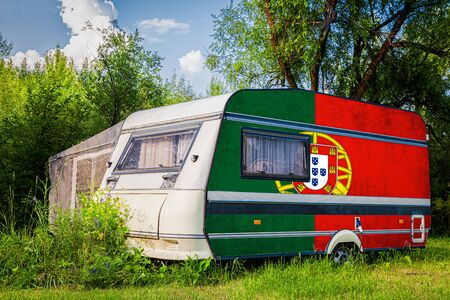 A car trailer, a motor home, painted in the national flag of Portugal stands parked in a mountainous. The concept of road transport, trade, export and import between countries.