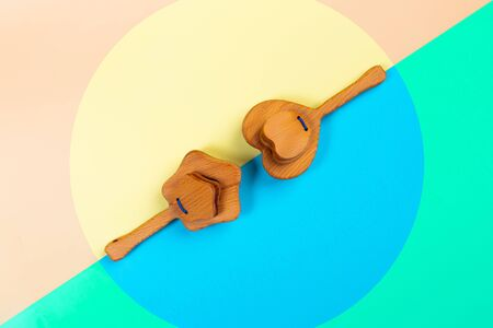Minimalistic flat lay with a wooden rattle  heart, star of beech  on an isolated multicolored vibrant geometric background. Toy for entertaining children and parents Stockfoto