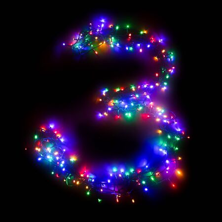 "Arabic numeral ""3"" from a multi-colored electric garland on a black isolated background. New year numbers. A wreath of colored light bulbs. Congratulations frame concept"