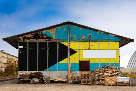 Close-up of the national flag of Bahamas  painted on the metal wall of a large warehouse the closed territory on a summer day. The concept of storage of goods, entry to a closed area, tourism