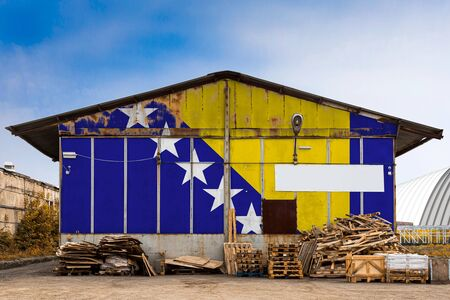 Close-up of the national flag of Bosnia Herzegovina painted on the metal wall of a large warehouse the closed territory on a summer day. The concept of storage of goods, entry to a closed area, tourism Imagens