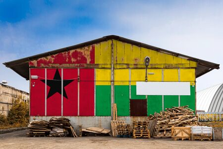 Close-up of the national flag of Guinea Bissau painted on the metal wall of a large warehouse the closed territory on a summer day. The concept of storage of goods, entry to a closed area, tourism