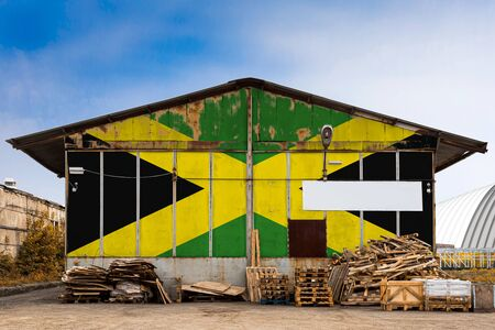 Close-up of the national flag of Jamaica painted on the metal wall of a large warehouse the closed territory on a summer day. The concept of storage of goods, entry to a closed area, tourism