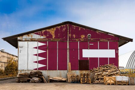 Close-up of the national flag of Qatar painted on the metal wall of a large warehouse the closed territory on a summer day. The concept of storage of goods, entry to a closed area, tourism