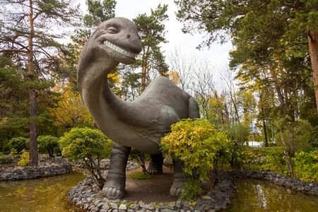 A large gray adult brachiosaurus looks towards the frame and stands on the stone bank of the river, next to small trees and shrubs on a warm autumn day. Dinosaur world