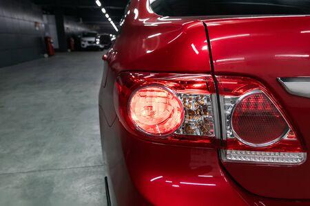 Back view of new red  city sedan. Closeup headlights of car  SUV. Modern rear light closeup. Car lamp close-up. Standard-Bild - 130957066