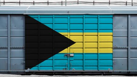 Front view of a container train freight car with a large metal lock with the national flag of Bahamas.The concept of export-import,transportation, national delivery of goods and rail transportation Standard-Bild - 130957096