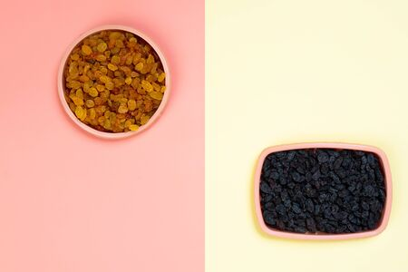 Minimalistic flat bark with plastic plates with yellow and black raisins on a yellow-pink isolated background. The concept of choosing food, right or bad. the concept of tasty and proper food Фото со стока