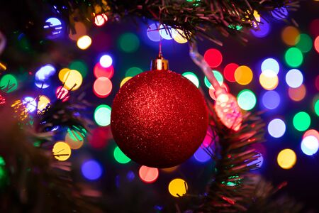 Close-up of a red shiny Christmas ball hanging on a Christmas tree in the background a lot of garlands glowing in different colors. New Year and Christmas concept. Beautifully decorated Christmas tree Фото со стока
