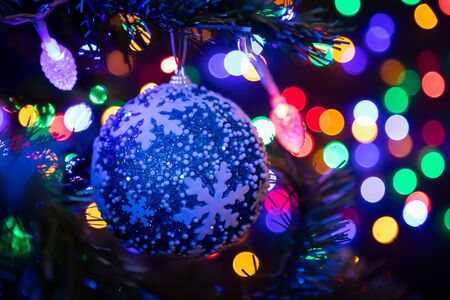 Close-up of a blue shiny Christmas ball hanging on a Christmas tree in the background a lot of garlands glowing in different colors.New Year and Christmas concept.Beautifully decorated Christmas tree Фото со стока