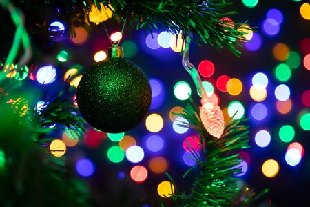 Close-up of a green shiny Christmas ball hanging on a Christmas tree in the background a lot of garlands glowing in different colors.New Year and Christmas concept.Beautifully decorated Christmas tree