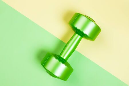 Minimalistic sports flat bark with a green dumbbell on a geometric green,  yellow isolated background. Sports fun concept.