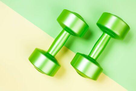 Minimalistic sports flat bark with a green dumbbells on a geometric  green,  yellow isolated background. Sports fun concept. Фото со стока