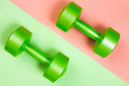 Minimalistic sports flat bark with a green dumbbells on a geometric pink, green isolated background. Sports fun concept. Фото со стока