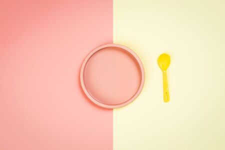 Minimalistic flat bark with a plastic pink plate and a yellow spoon in a yellow-pink isolated background. Plastic tableware with place for your text, moсup. Dishes for childrens games