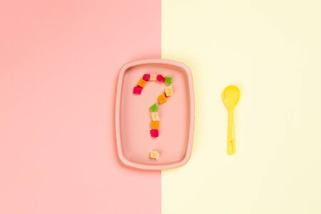 Minimalistic flat bark with a plastic pink plate on which is a question mark of candied pineapple and a yellow spoon in a yellow-pink isolated background. The concept of choosing food, right or bad