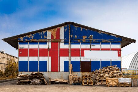 Close-up of the national flag of Iceland  painted on the metal wall of a large warehouse the closed territory on a summer day. The concept of storage of goods, entry to a closed area, tourism