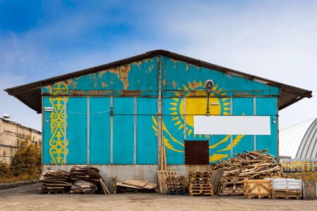 Close-up of the national flag of Kazakhstan painted on the metal wall of a large warehouse the closed territory on a summer day. The concept of storage of goods, entry to a closed area, tourism