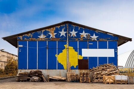 Close-up of the national flag of Kosovo  painted on the metal wall of a large warehouse the closed territory on a summer day. The concept of storage of goods, entry to a closed area, tourism Stock fotó