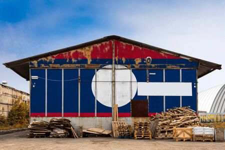 Close-up of the national flag of Laos  painted on the metal wall of a large warehouse the closed territory on a summer day. The concept of storage of goods, entry to a closed area, tourism