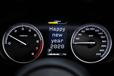 Close up Instrument automobile panel with Odometer, speedometer, tachometer, fuel level, which says Happy New Year 2020. The concept of the new year and Christmas in the automotive field