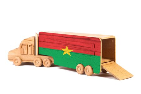 Close-up of a wooden toy truck with a painted national flag Burkino Faso. The concept of export-import,transportation, national delivery of goods