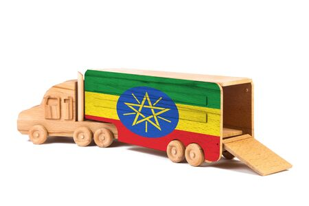Close-up of a wooden toy truck with a painted national flag Ethiopia. The concept of export-import,transportation, national delivery of goods