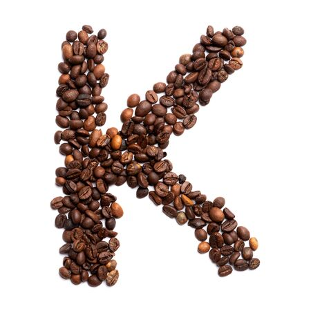 Letter K of the English alphabet of freshly roasted cocoa beans on a white isolated background. coffee pattern made from coffee beans. Font for coffein, the concept of vivacity and culture of coffee. Writing Letters 版權商用圖片