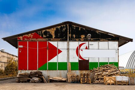 Close-up of the national flag of West Sahara painted on the metal wall of a large warehouse the closed territory on a summer day. The concept of storage of goods, entry to a closed area, tourism