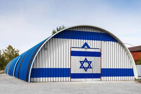 Close-up of the national flag of Israel painted on the metal wall of a large warehouse the closed territory against blue sky. The concept of storage of goods, entry to a closed area, logistics
