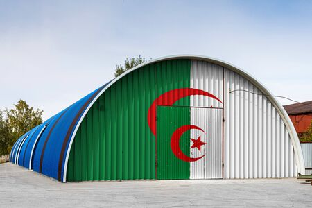 Close-up of the national flag of Algeria painted on the metal wall of a large warehouse the closed territory against blue sky. The concept of storage of goods, entry to a closed area, logistics