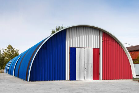 Close-up of the national flag of France  painted on the metal wall of a large warehouse the closed territory against blue sky. The concept of storage of goods, entry to a closed area, logistics