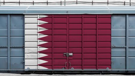 Front view of a container train freight car with a large metal lock with the national flag of Qatar.The concept of export-import,transportation, national delivery of goods and rail transportation